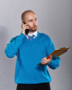 Businessman talking on cell phone in shirt and tie and holding a folder with papers business people concept of success Stock Images