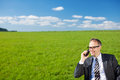 Businessman talking on his mobile in nature standing suit a beautiful open green grassy field under a sunny blue sky Stock Image