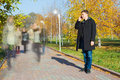 Businessman talking on mobile phone in the park young motion blurred people walking Stock Photos