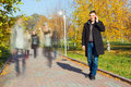Businessman talking on mobile phone in the park young motion blurred people walking Stock Photo