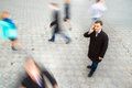 Businessman talking on mobile phone young attractive motion blurred commuters walking to work Stock Images