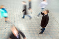 Businessman talking on mobile phone young attractive motion blurred commuters walking to work Stock Photos