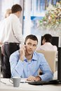Businessman talking on mobile sitting at desk in office phone Stock Images