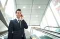 Businessman talking on the phone on escalator close up portrait of a happy Royalty Free Stock Images
