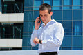 Businessman talking on the phone in front of modern building businessman in a hurry looking at his watch Royalty Free Stock Images