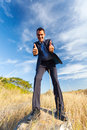 Businessman thumbs up cheerful young on top of rock giving outdoors Stock Image