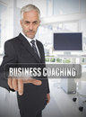 Businessman touching the term business coaching in his office Royalty Free Stock Images