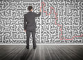Businessman tracing a red line on a maze drew the wall Royalty Free Stock Photos