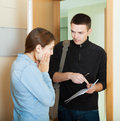 Businessman trying to collect money from housewife at home door focus on woman Stock Photos
