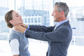 Businessman trying to smother his colleague in the office Stock Images