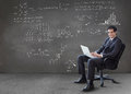 Businessman typing on his laptop with maths equations on wall in grey empty room Royalty Free Stock Photo