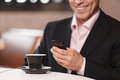 Businessman typing a message cropped image of businessman drink drinking coffee and in his mobile phone Royalty Free Stock Image