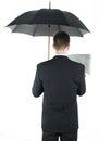 Businessman with an umbrella reading a newspaper Stock Photos
