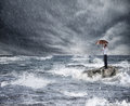 Photo : Businessman with umbrella during storm in the sea. Concept of insurance protection end tax coin