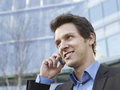 Businessman using cell phone outside office building closeup of happy young Royalty Free Stock Photos