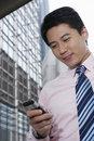 Businessman using cell phone outside office building low angle view of handsome young Stock Photography