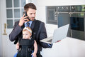 Businessman using cellphone and laptop while carrying daughter Royalty Free Stock Photo