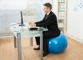 Businessman using computer while sitting on pilates ball Royalty Free Stock Photo