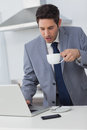 Businessman using his laptop while drinking coffee in the kitchen Royalty Free Stock Images