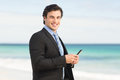 Businessman using his smartphone at the beach Royalty Free Stock Images