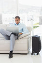 Businessman using laptop sitting on sofa waiting to depart on business trip in the office Stock Photos