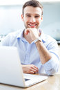 Businessman using laptop and smiling Stock Photo