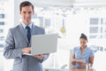 Businessman using laptop standing in office smiling at camera