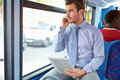 Businessman using mobile phone and digital tablet on bus looking out window Stock Photography