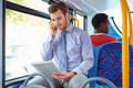 Businessman using mobile phone and digital tablet on bus with passenger in background Stock Images