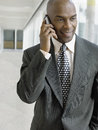 Businessman using mobile phone while looking down in office an african american Royalty Free Stock Photography