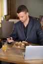 Businessman using mobilephone while having food young in cafe Royalty Free Stock Photos