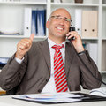 Businessman using phone while gesturing thumbs up happy mature landline at office desk Stock Images