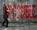 Businessman using sledgehammer cracking red impossible word brok broken on concrete wall background Stock Photos