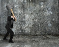 Businessman using sledgehammer cracking wall broken on concrete floor background Stock Photography