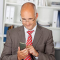 Businessman using smartphone in the office portrait of Stock Images