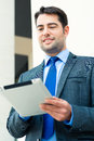 Businessman using tablet computer or manager pad or reading or presenting on it Royalty Free Stock Images