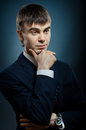 Businessman vertical portrait the young in costume fixed look on dark blue background Royalty Free Stock Photo