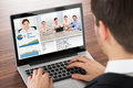 Businessman video conferencing on laptop with colleague in office Stock Photo