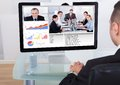 Businessman video conferencing with team rear view of on computer in office Royalty Free Stock Photo