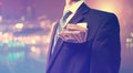 Businessman with wad of cash on blurred city background Stock Photography