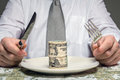 Businessman with wad of dollars served on plate sitting behind a table fork and knife ready to eat a business concept Royalty Free Stock Photography