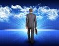 Businessman walking against blue landscape with
