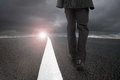 Businessman walking on asphalt road with sunlight cloudy sky Royalty Free Stock Photo