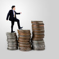 Businessman walking on coins stack on gray Royalty Free Stock Photo