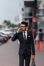 Businessman walking down the street and talking on the phone. Blurred motion Royalty Free Stock Photo