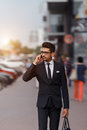 Businessman walking down the street and talking on the phone  with early sunlight. Blurred motion Royalty Free Stock Photo