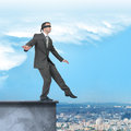 Businessman walking from edge of building roof Royalty Free Stock Photo
