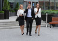 Businessman walking on the street with their secretaries in front of office Stock Photos