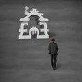 Businessman walking toward money symbol stacking building Royalty Free Stock Photo