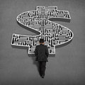 Businessman walking toward to d money shape maze on concrete ground Royalty Free Stock Photo